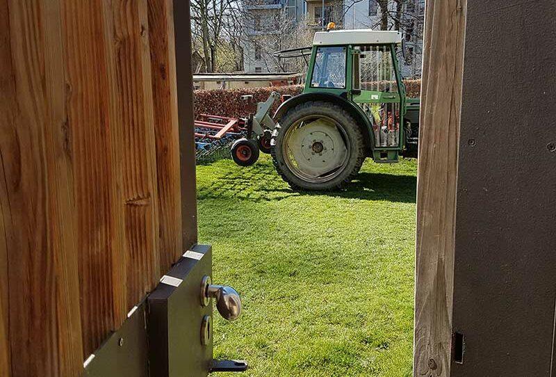 Blick auf einen Traktor nach dem Striegeln im Roggen durch einen Notausgang